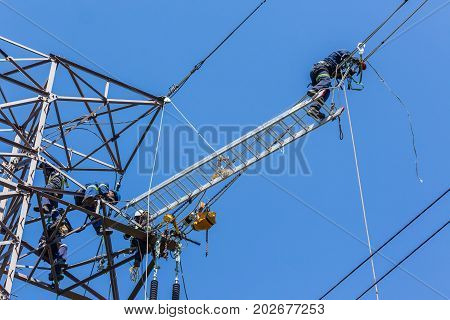 Electricians high up suspended on electrical steel tower installing new high voltage electricity powerlines.