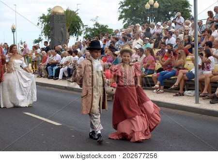 FUNCHAL MADEIRA PORTUGAL - SEPTEMBER 4 2016: Group of people in historical fashion dress durnig historical and ethnographic parade of Madeira Wine Festival in Funchal. Madeira Portugal