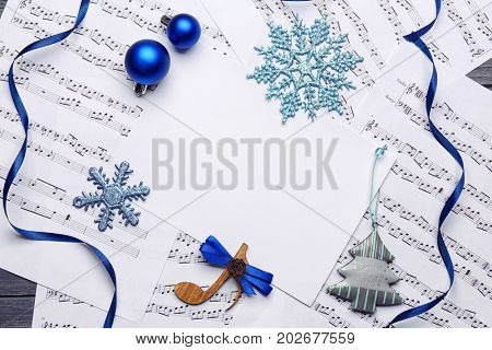 Beautiful composition with paper card and decorations on music sheets. Christmas songs concept
