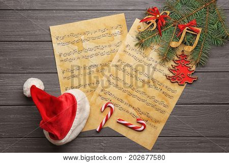 Beautiful composition with decorations and music sheets on wooden background. Christmas songs concept
