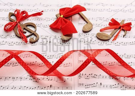 Beautiful composition with wooden decorations on music sheets. Christmas songs concept