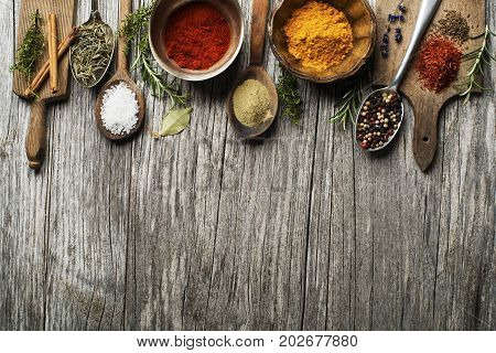 Fresh herbs and spices on a wooden background