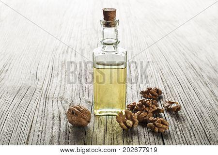 Walnut oil in a glass bottle on a wooden background