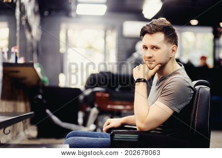 Man looks at the frame in barbershop. Copy space