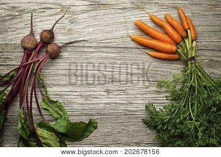Fresh vegetables of carrots and red beets on wooden background