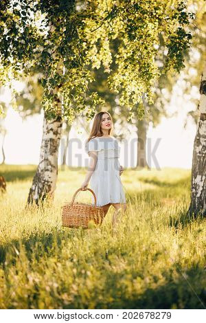 pregnant girl in a light dress is walking through the woods with a basket. Concept maternity, pregnancy, childbirth, walk in the park. Sunset