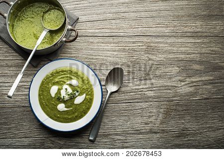 Fresh healthy green soup on wooden background overhead shoot.