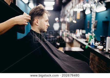 Man is smiling in hairdresser's barber shop.