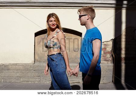 Cute happy couple holding hands while having nice morning walk. Pretty girl in stylish summer clothes smiling having palyful mysterious look leading her bearded boyfriend by the hand outdoors