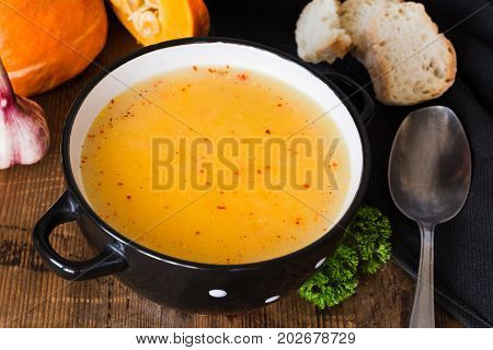 Pumpkin cream soup with red pepper flakes in bowl. Closeup view. Autumn comfort food