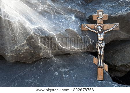 Silhouette of the crucified Jesus Christ on the cross in the rays of light against the background of granite stones. The biblical prophet is the symbol of death. Mountain Calvary Christmas Easter background.