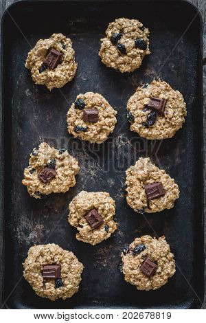 Freshly baked oatmeal raisin cookies with dark chocolate, cinnamon and nuts on old rusty cookie sheet. Table top view, vertical composition