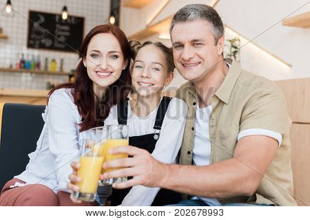 beautiful family clinking with glasses of juice in cafe