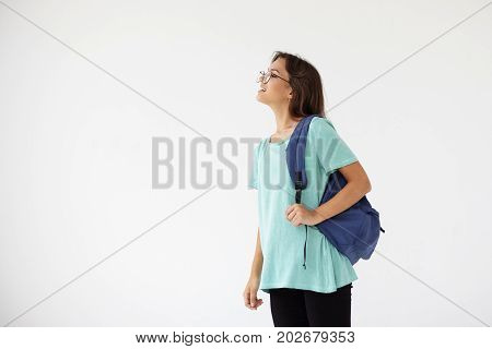 Profile shot of beautiful casually dressed mixed race student girl wearing eyeglasses and rucksack looking in front of her and smiling cheerfully. People learning education and youth concept