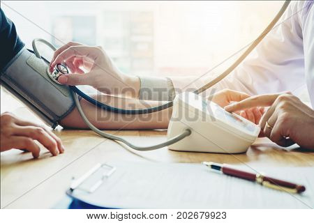 Doctor Measuring Arterial Blood Pressure Woman Patient On Arm Health Care In Hospital