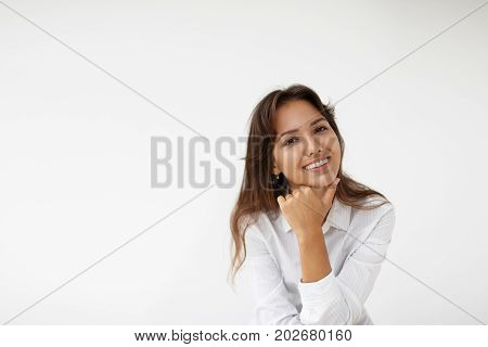 Positive emotions and genuine feelings. Headshot of happy carefree young mixed race female with long brown hair and cute charming smile posing in studio her eyes expressing joy and happiness
