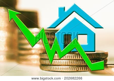 The graph of growth and a symbol of real estate on a background of money . The concept of changes in property prices .