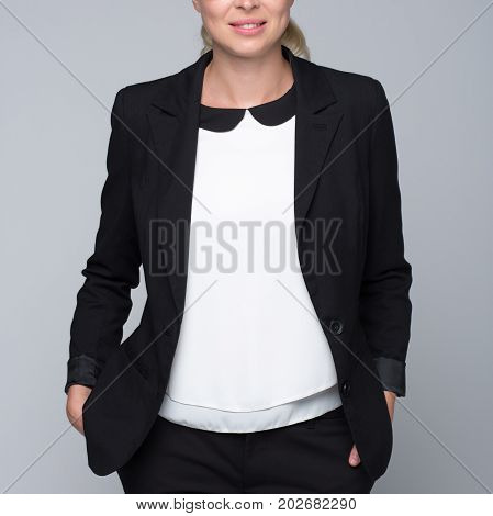 Torso of businesswoman in business attire. Style portrait on grey background.