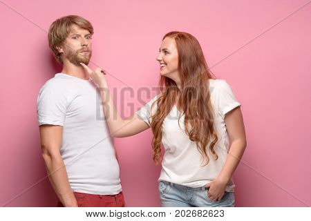 The photo of beautiful couple, studio shoot. The girl seducing a guy
