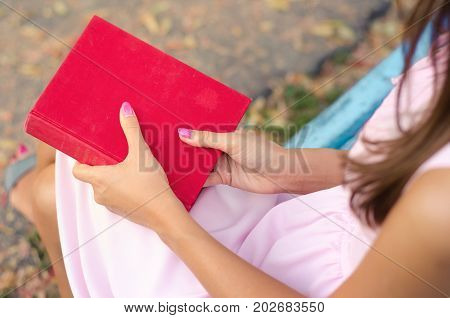 Student girl holding a red book. A woman with book lying on her lap on a park bench.