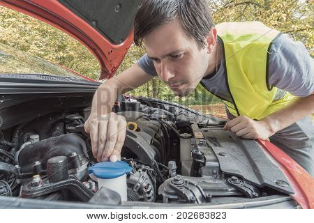 Man is repairing car and checking engine coolant.