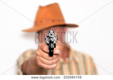 Cowboy man in hat with revolver gun isolated on white. Man with the gun aiming at the screen.