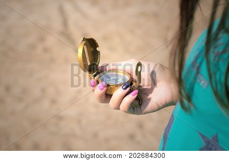 Tourist woman holding compass in hands close up. Travel concept.