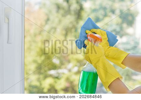 Woman cleaning window with blue cloth. Glass cleaning