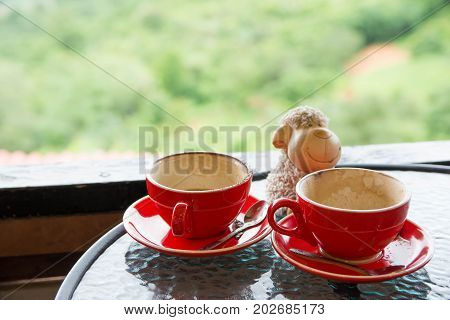 Two empty red cup with cute lamb resin nearby on glass table in coffee shop with green natural mountain as background.