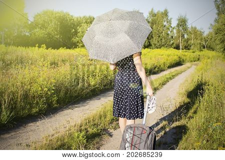 girl in polka dot dress under the scorching sun to walk along the forest road. City girl arrived in the village