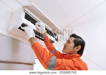 Young Asian Male Technician Repairing Air Conditioner