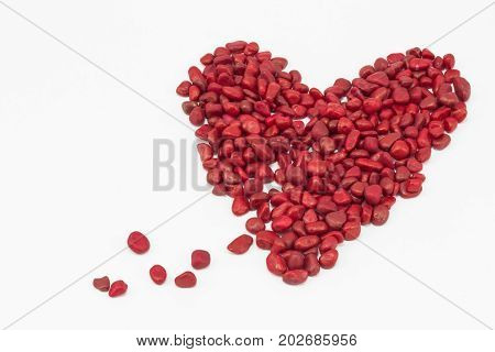 A bleeding heart made by little red stones put one next to the other on a white surface.
