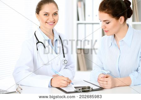 Friendly smiling doctor  and  patient sitting at the table. Very good news and high level medical service concept.