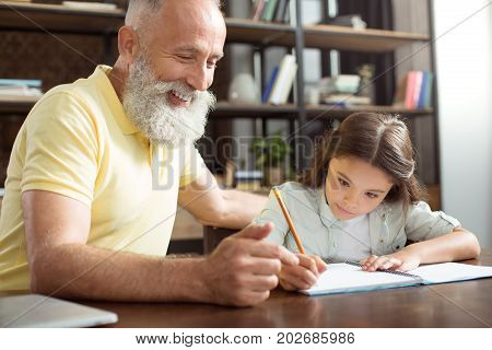 Pleasure to help. Charming elderly man sitting next to his pretty little granddaughter doing her home assignment and helping her by giving advice