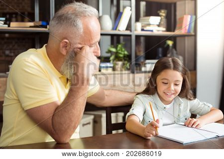 Loving helper. Pleasant elderly man sitting next to his little granddaughter and listening to her revising her home assignment