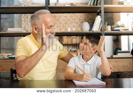 Team spirit. Adorable little boy sitting at the table next to his grandfather and giving him a high five while doing home assignment
