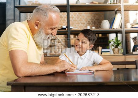 Helpful advice. Cheerful senior man with a grey beard pointing at the notebook of his beloved grandson doing home assignment while giving him a tip on doing sums