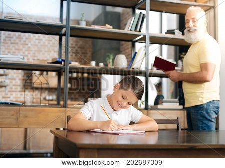 Helpful tutor. Charming senior man holding a book and dictating a text passage from it while his grandson putting it down, practicing spelling