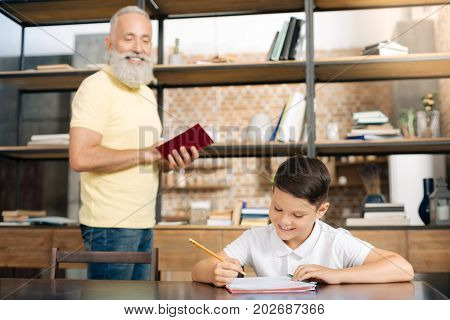 Best tutor. Pleasant elderly man holding a book and dictating a passage from text to his beloved little grandson while he putting it down