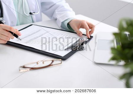 Close-up of a female doctor filling out application form , sitting at the table in the hospital.
