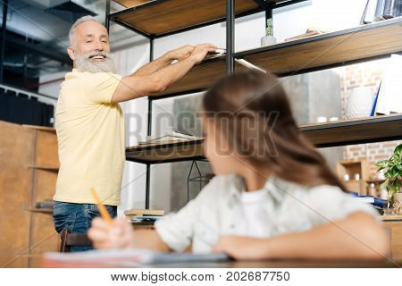 I am on it. The focus being on a charming elderly man taking a book from the shelf while smiling at his granddaughter doing home assignment at the table