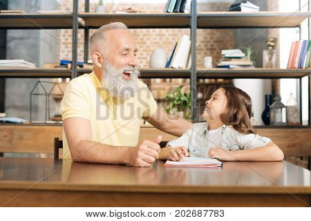 Precious moments. Adorable little girl and her beloved grandfather sitting at the table and laughing happily together while the girl doing her home assignment