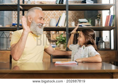 Great job. Lovely little girl sitting at the table next to her beloved grandfather and giving him a high five while exchanging smiles with him