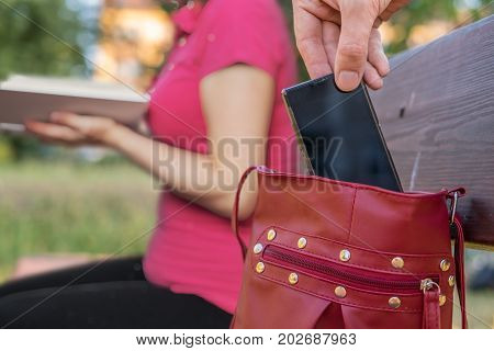 Thief is stealing smartphone from bag of a woman sitting on bench.