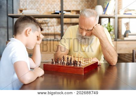 Engaged in game. Concentrated serious grandfather sitting at the table with his pre-teen grandson and playing chess with him, carefully thinking about next moves