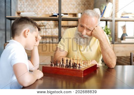 Patiently waiting. Pleasant senior man playing chess with his adorable pre-teen grandson and looking at him with smile, waiting for his next move