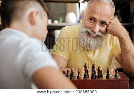 Enjoying the game. Joyful charming man sitting at the table, resting his head on the hand and smiling at his grandson thinking about his next move in the chess game
