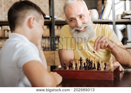 Glad to play. Handsome elderly man with a grey beard holding a pawn in his hand and making next move in a chess game with his beloved grandson