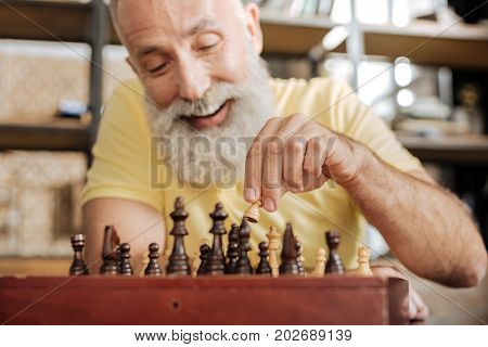 Training brain. Pleasant elderly man with a grey beard holding a pawn in his hand and being about to make a move with it while smiling happily