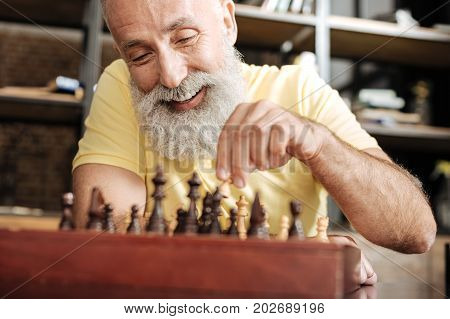 Brain game. Cheerful elderly man with a grey beard moving a pawn across a chessboard and smiling, obviously enjoying the game